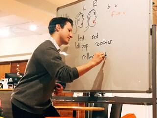 先生が明るい部屋でホワイトボードに書いている