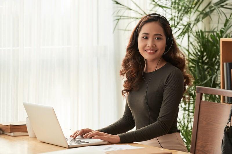 若い女性がパソコンを使用しながら何かを聞いている